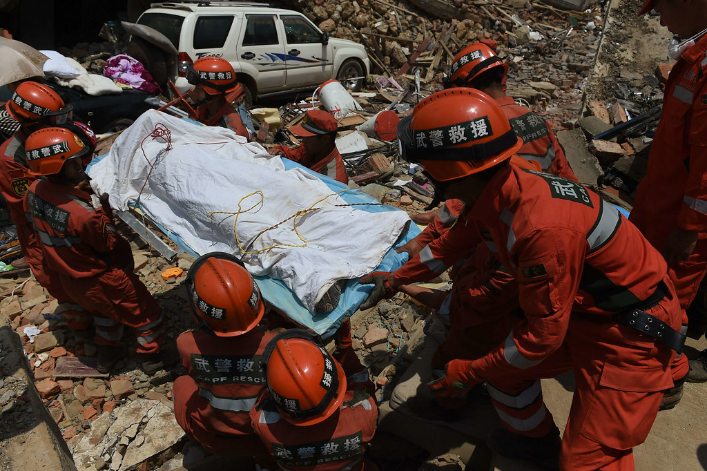 . Rescuers recover a body from a collapsed house at Longtoushan, in China\'s southwest Yunnan province on August 5, 2014. AFP PHOTO/Greg BAKER/AFP/Getty Images