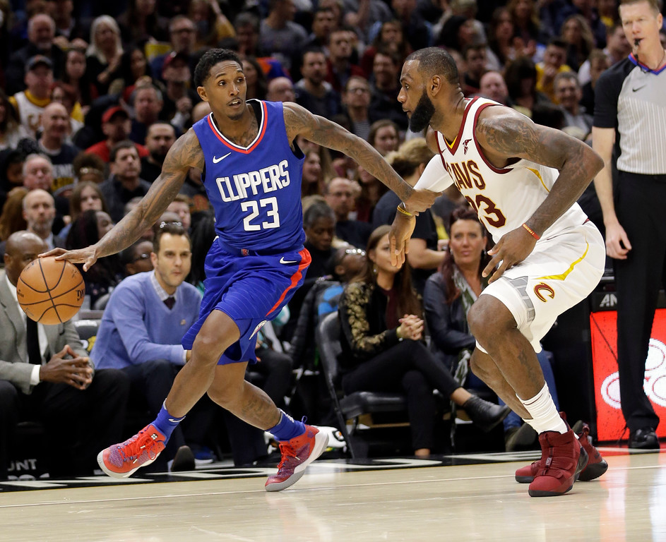 . Los Angeles Clippers\' Lou Williams, left, drives past Cleveland Cavaliers\' LeBron James in the second half of an NBA basketball game, Friday, Nov. 17, 2017, in Cleveland. The Cavaliers won 118-113 in overtime. (AP Photo/Tony Dejak)
