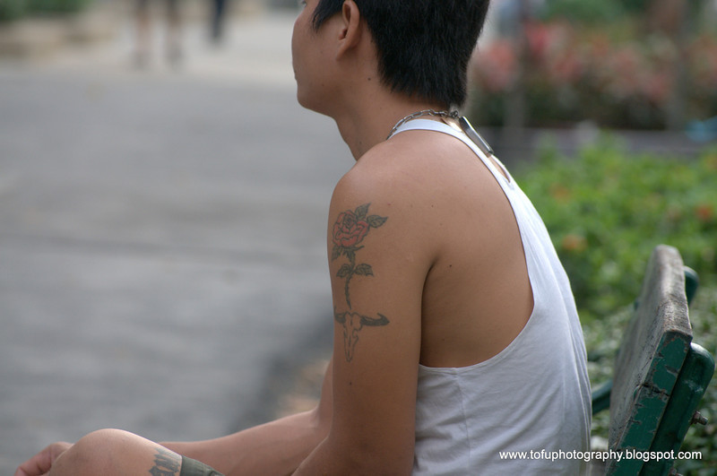 Man watching volleyball in a park near the Chao Praya River in Thonburu, Bangkok, Thailand in December 2009. A strange combination of tattoos, a rose and an buffalo as well as a religious one on his thigh!