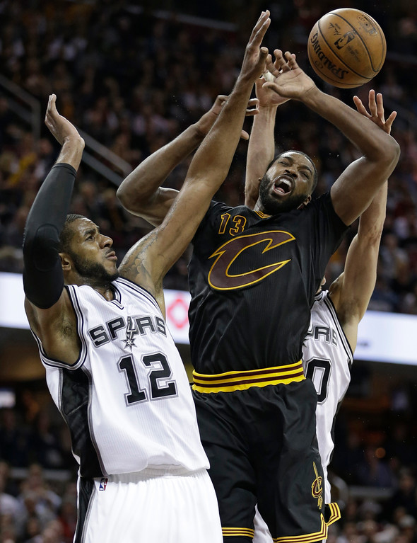 . Cleveland Cavaliers\' Tristan Thompson (13) loses control of the ball against San Antonio Spurs\' LaMarcus Aldridge (12) during the second half of an NBA basketball game, Saturday, Jan. 21, 2017, in Cleveland. Manu Ginobili defends from behind. The Spurs won 118-115 in overtime. (AP Photo/Tony Dejak)
