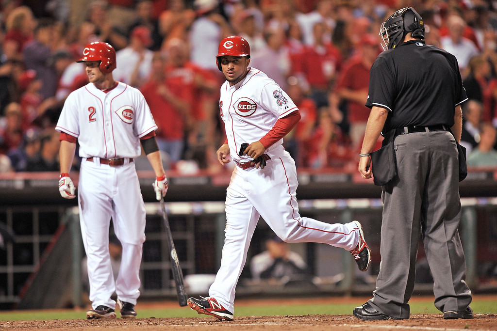 . Cesar Izturis #3 of the Cincinnati Reds crosses home plate for the Reds\' fourth run after pitcher Edgmer Escalona #61 of the Colorado Rockies balked in the seventh inning at Great American Ball Park on June 4, 2013 in Cincinnati, Ohio. Colorado defeated Cincinnati 5-4.  (Photo by Jamie Sabau/Getty Images)