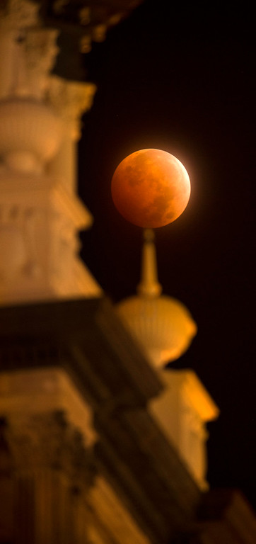 . A lunar eclipse appears above the Pioneers Museum in downtown Colorado Springs, Colo., early Wednesday morning, Oct. 8, 2014. (AP Photo/The Colorado Springs Gazette, Mark Reis)