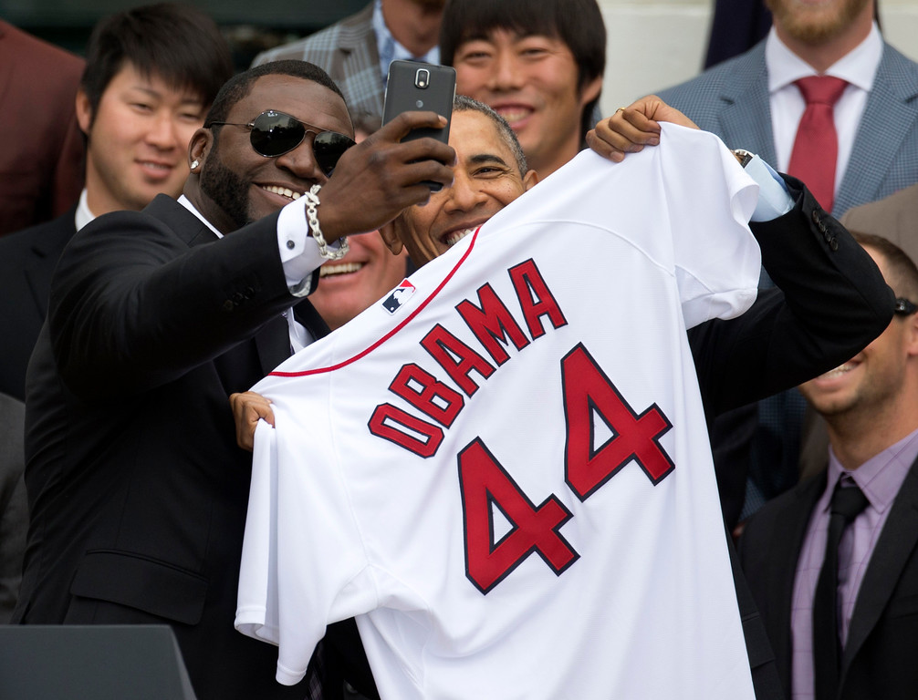 ". Boston Red Sox player David ""Big Papi\"" Ortiz takes a selfie with President Barack Obama, holding a Boston Red Sox jersey presented to the president during a ceremony on the South Lawn of the White House in Washington, Tuesday, April 1, 2014, where the president honored the 2013 World Series baseball champion Boston Red Sox. In the background are pitchers Junichi Tazawa, left, Koji Uehara, right.  (AP Photo/Carolyn Kaster)"