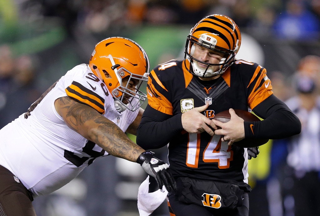 . Cincinnati Bengals quarterback Andy Dalton (14) is tackled by Cleveland Browns defensive end Billy Winn (90) during the second half of an NFL football game Thursday, Nov. 6, 2014, in Cincinnati. (AP Photo/Michael Conroy)