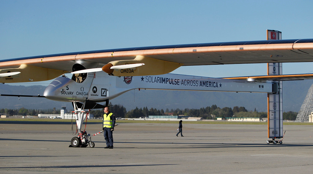 . The ground crew tends to the Solar Impulse, the experimental airplane, after it made a test flight at Moffett Airfield in Mountain View, Calif. Friday morning April 19, 2013.  (Patrick Tehan/Staff)