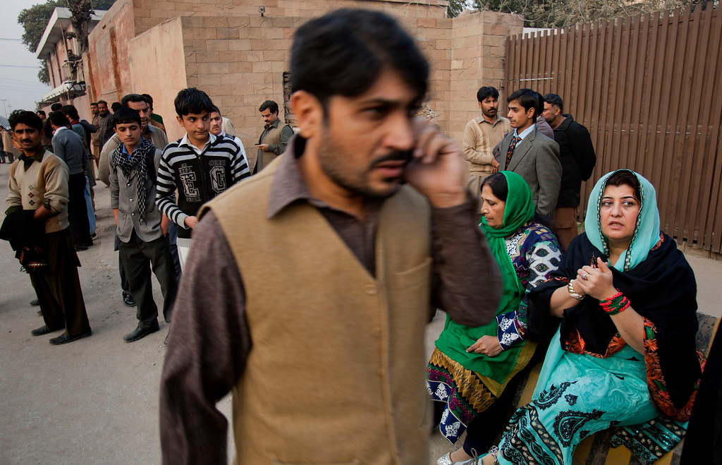 . People wait for their children outside a school attacked by the Taliban in Peshawar, Pakistan, Tuesday, Dec. 16, 2014. Taliban gunmen stormed a military-run school in the northwestern Pakistani city of Peshawar on Tuesday, killing and wounding scores, officials said, in the highest-profile militant attack to hit the troubled region in months. (AP Photo/B.K. Bangash)