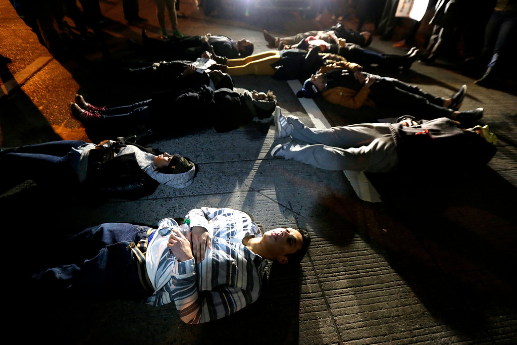 . People lie in the middle of the West Side Highway during a protest after it was announced that the New York City police officer involved in the death of Eric Garner was not indicted, Wednesday, Dec. 3, 2014, in New York. A grand jury cleared the police officer Wednesday in the videotaped chokehold death of Garner, an unarmed black man, who had been stopped on suspicion of selling loose, untaxed cigarettes. (AP Photo/Julio Cortez)