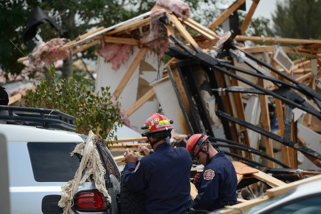 . Members of the North Area Tech Rescue Team, left, stand in the debris scattered from a house explosion on the 9300 block of Ingalls Street in Westminster, Colorado, Thursday afternoon June 13, 2013.  (Photo By Andy Cross/The Denver Post)