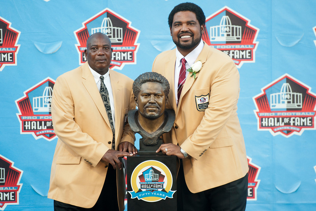 . CANTON, OH - AUGUST 3: Baltimore Ravens General Manager/Executive Vice President and Hall of Fame tight end, Ozzie Newsome (L), presents former offensive lineman Jonathan Ogden of the Baltimore Ravens with his Hall of Fame bust during the NFL Class of 2013 Enshrinement Ceremony at Fawcett Stadium on Aug. 3, 2013 in Canton, Ohio. (Photo by Jason Miller/Getty Images)