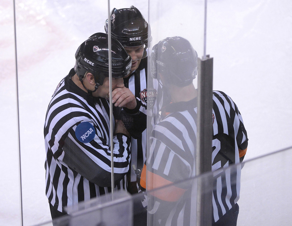 . DENVER, CO. - FEBRUARY 21, 2014: Officials deliberated on a game misconduct call on Denver wing  Zac Larraza in the second period. The University of Denver hockey team hosted Colorado College at Magness Arena Friday night, February 21, 2014. Photo By Karl Gehring/The Denver Post