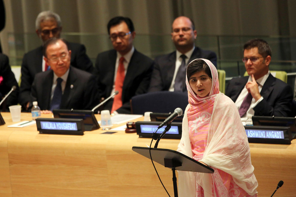 """. United Nations Secretary-General Ban Ki-moon, left, listens as  Malala Yousafzai, right, addresses the \""""Malala Day\"""" Youth Assembly, at United Nations headquarters on Friday, July 12, 2013. A year ago, Malala Yousafzai was a schoolgirl in northwest Pakistan. Today she\'s the world-famous survivor of a Taliban assassination attempt, an activist for girls\' education and a contender to win the Nobel Peace Prize on Friday Oct. 11, 2013. (AP Photo/Mary Altaffer, File)"""