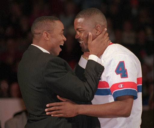 Description of . Former Detroit Piston Isiah Thomas gets a hug from his former teammate and current Piston, Joe Dumars during a ceremony to retire Thomas' number at the Palace of Auburn Hills, Mich., Saturday, Feb. 17, 1996. Thomas played 979 games in 13 seasons with the Pistons. He was selected to the NBA All-Star game 12 times and helped his team win the NBA World Championship twice. (AP Photo/Jeff Kowalsky)
