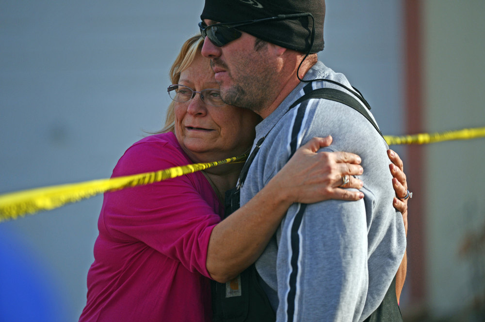 . Residents console each other, Tuesday, December 18, 2012, in a neighborhood where four people were found dead in a home in Longmont. RJ Sangosti, The Denver Post
