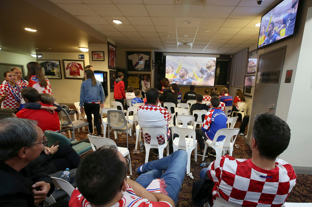 . Croatia fans at the King Tom Club in Sydney, Australia, watch France celebrate after the soccer World Cup final between France and Croatia, Monday, July 16, 2018. (AP Photo/Rick Rycroft)