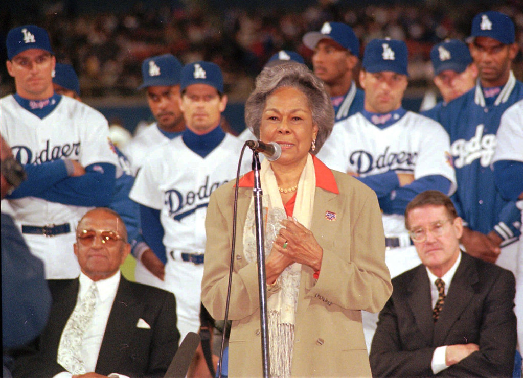 ". Rachel Robinson, widow of the late baseball great Jackie Robinson, speaks during the ""Salute to Jackie Robinson Night\"" at Dodger Stadium in Los Angeles Saturday, April 5, 1997.  The salute paid tribute to the 50th anniversary of Robinson\'s historic debut with the Brooklyn Dodgers, which broke major league baseball\'s color barrier.  Seated behind Rachel are Robinson\'s former teammate Don Newcombe, left, and Dodgers owner Peter O\'Malley.  (AP Photo/Steve Grason)"