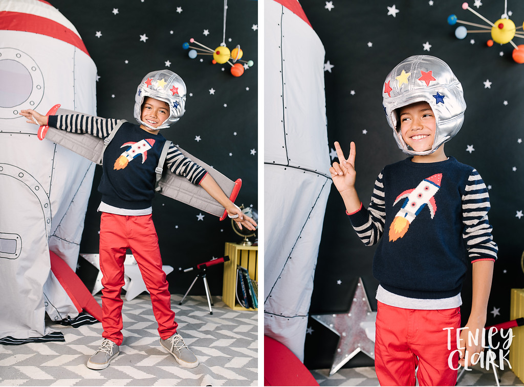 Playful studio portraits of little boy with colorful outerspace themed room and clothing. Commercial photography by Tenley Clark.