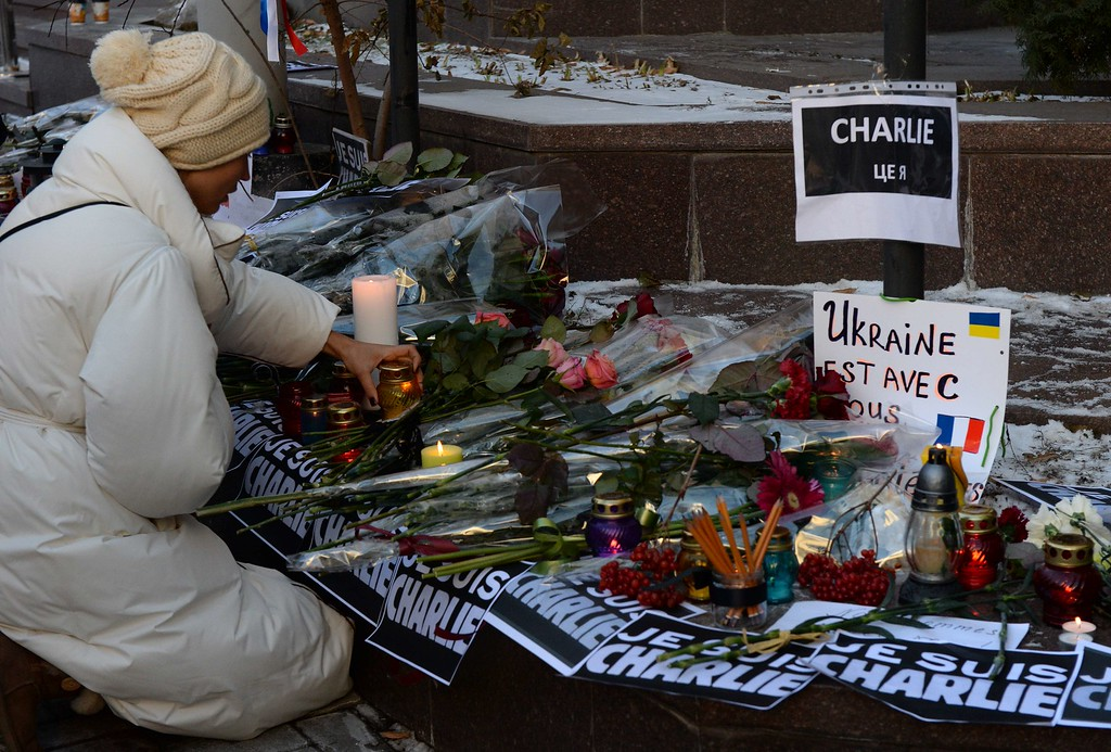 . A woman lays a candle in front of the French embassy in Kiev on January 8, 2015, in tribute to the twelve people killed the day before in an attack by two armed gunmen on the offices of French satirical newspaper Charlie Hebdo in Paris. A stunned and outraged France was in mourning today, as security forces desperately hunted two brothers suspected of gunning down 12 people in an Islamist attack on a satirical weekly. AFP PHOTO / VASILY MAXIMOV/AFP/Getty Images
