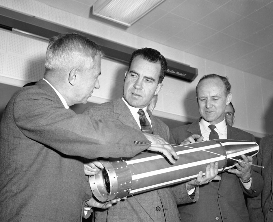 . Vice President Richard Nixon looks at a model of the Explorer satellite with Dr. Lee DuBridge,left, president of Cal Tech, and Dr. William H. Pickering, right, director of the Cal Tech Jet Propulsion lab, during a news conference in Pasadena, Calif., Feb. 17, 1958.  (AP Photo)