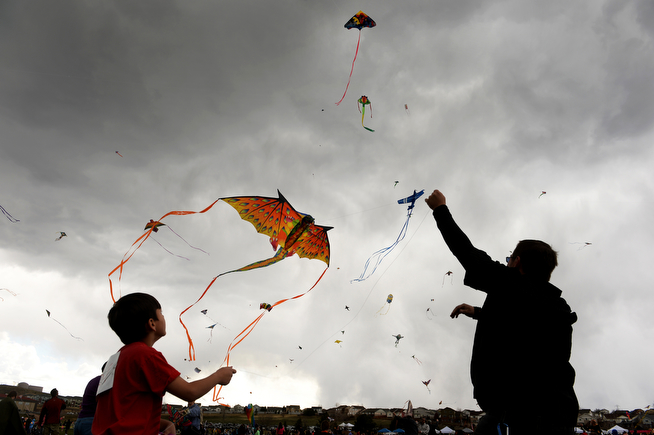 . Carlos Vallejos, 8, left and his cousin Chris Beam, right, of Denver, Vasalisa  try to get Vallejos\'  dragon kite in the air during the 12th annual Arvada Kite Festival held at the Stenger soccer complex in Arvada, Co on April 6, 2014.  Hundreds of people braved cold temperatures , some rain and gusty winds to fly their kites  of all different sizes, shapes, and colors. Activities included kite making classes and competitions for highest kite, smallest kite, largest kite and most visually appealing kite.  (Photo By Helen H. Richardson/ The Denver Post)