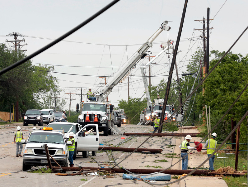 . Utility workers try to restore electric power on down lines on Thursday, May 16, 2013, in Cleburne, Texas.  A rash of tornadoes slammed into several small communities in North Texas overnight, leaving at least six people dead, dozens more injured and hundreds homeless. The violent spring storm scattered bodies, flattened homes and threw trailers onto cars.  (AP Photo/The Dallas Morning News, Michael Ainsworth)