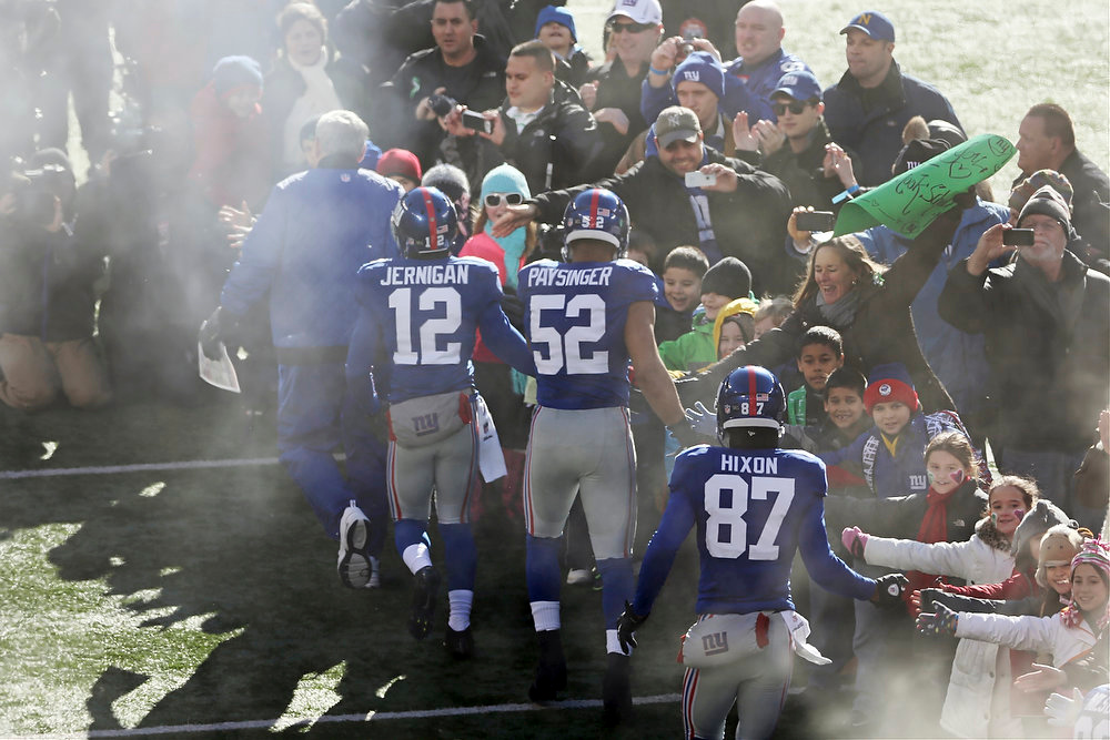 Description of . New York Giants wide receiver Jerrel Jernigan (12), Spencer Paysinger (52) and Domenik Hixon (87) greet a contingent of teachers, parents, and students from Sandy Hook Elementary School in Newtown, Conn., before an NFL football game Sunday, Dec. 30, 2012, in East Rutherford, N.J. The school was the site of a mass shooting on Dec. 14. (AP Photo/Peter Morgan)