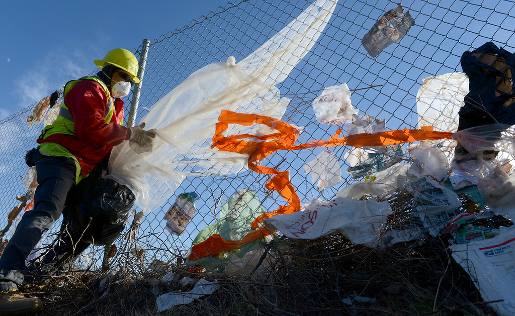 . Workers from Athens Service pull wind blown trash Monday December 9, 2013, from a fence bordering the 210 freeway in Fontana. Trash was stuck along nearly a mile of fence line. (Staff photo by Rick Sforza)