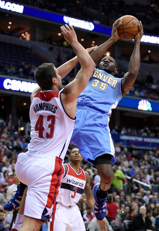 . Denver Nuggets forward Kenneth Faried (35) goes to the basket against Washington Wizards forward Kris Humphries (43) and Bradley Beal (3) during the first half of an NBA basketball game, Friday, Dec. 5, 2014, in Washington. (AP Photo/Nick Wass)