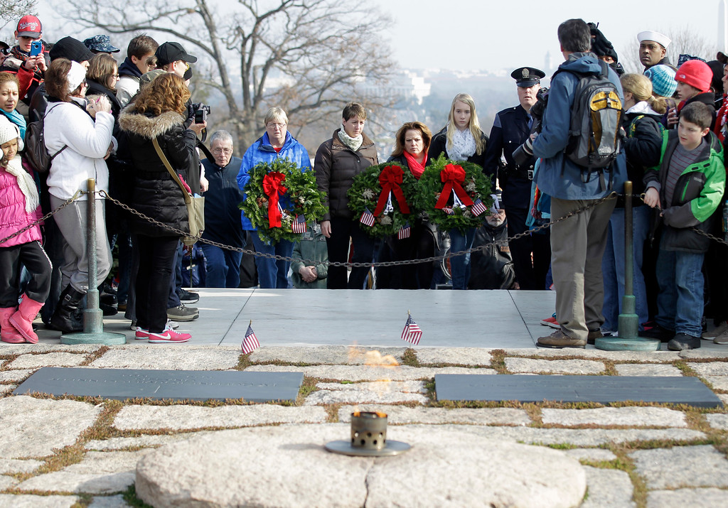 . Volunteers place holiday wreaths at the gravesite of President John F. Kennedy during Wreaths Across America\'s 150th anniversary, Saturday, Dec. 13, 2014, at Arlington National Cemetery in Arlington, Va. (AP Photo/Luis M. Alvarez)