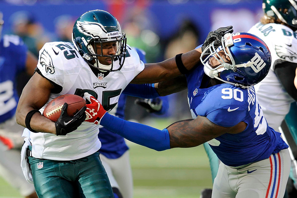 Description of . Philadelphia Eagles running back LeSean McCoy (25) stiff-arms New York Giants defensive end Jason Pierre-Paul (90) during the first half of an NFL football game on Sunday, Dec. 30, 2012, in East Rutherford, N.J. (AP Photo/Bill Kostroun)