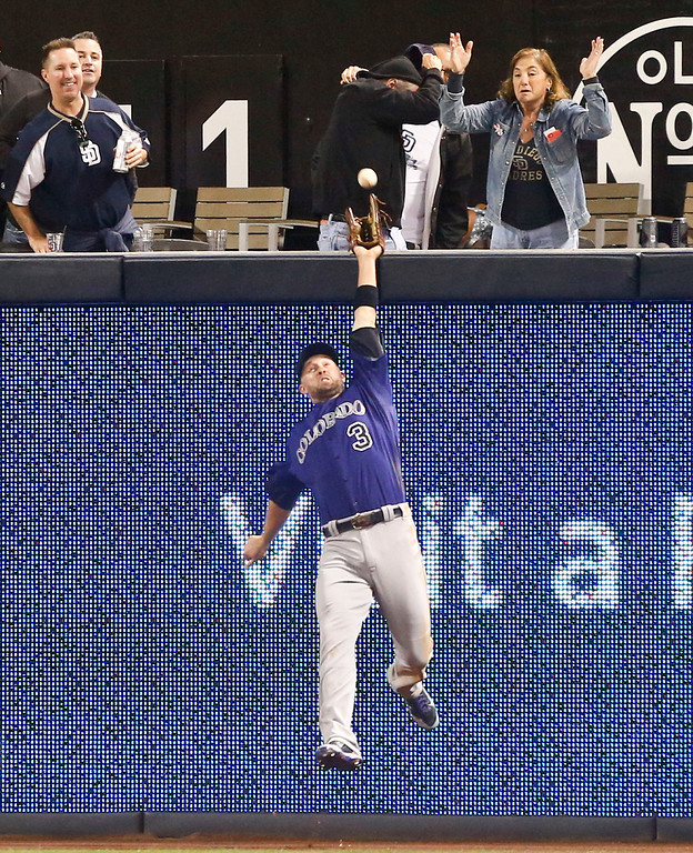 . Colorado Rockies right fielder Michael Cuddyer leaps trying to make a catch on a deep drive by San Diego Padres\' Alexi Amarista in the fifth inning of a baseball game Monday, April 14, 2014, in San Diego.  Cuddyer could not make the catch and Amarista got a triple on the play. (AP Photo/Lenny Ignelzi)