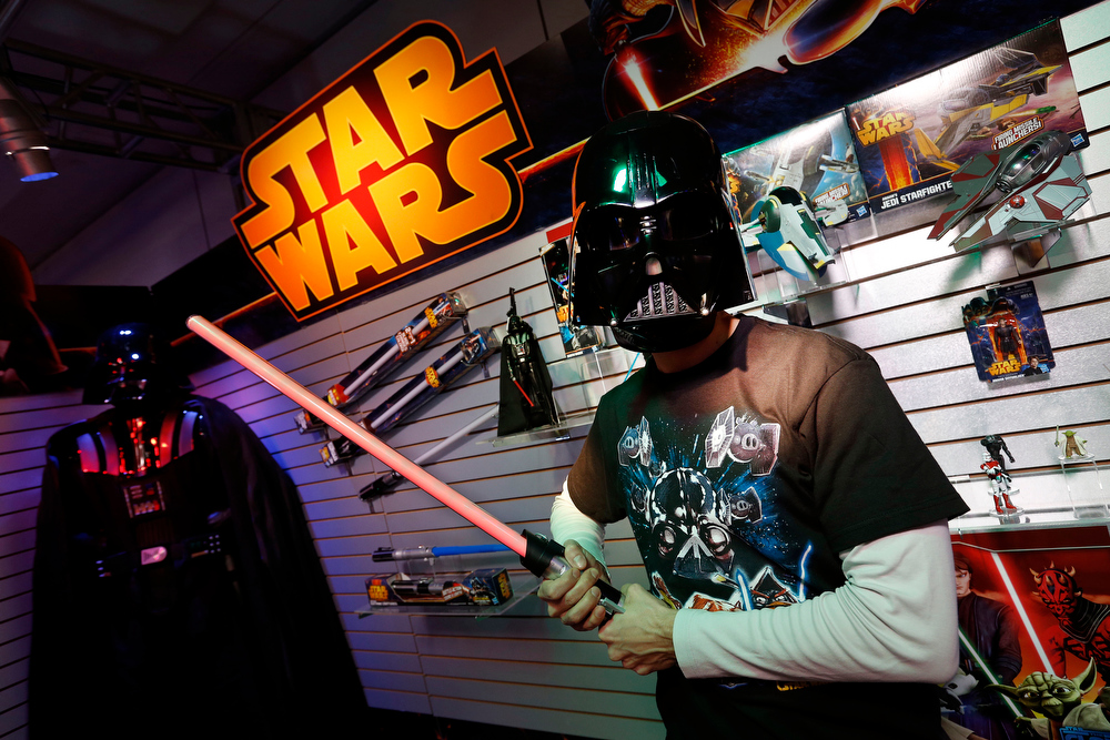 . Toy demonstrator Jeff Wolf gets in touch with his Dark Side wearing the STAR WARS DARTH VADER VOICE CHANGING HELMET and holding the STAR WARS ANAKIN TO DARTH VADER LIGHTSABER in Hasbroís showroom at the American International Toy Fair, Saturday, Feb. 9, 2013, in New York. (Photo by Jason DeCrow/Invision for Hasbro/AP Images)