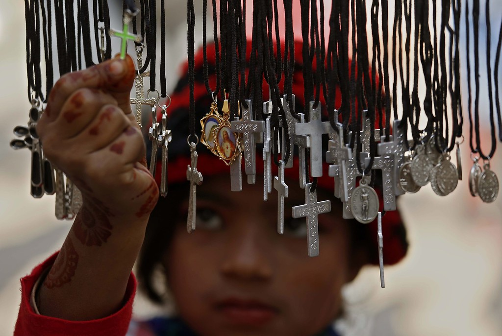 . A Pakistani Christian girl buys crosses during Christmas celebrations, in Peshawar, Pakistan, 25 December 2013. Christians in Pakistan form the largest minority community, with about 1,6 per cent of the population. December 25th is celebrated as birth anniversary of Lord Jesus Christ. Christmas is basically celebrated by the Christians but it is also observed as a day of celebration by other communities around the globe.  EPA/ARSHAD ARBAB