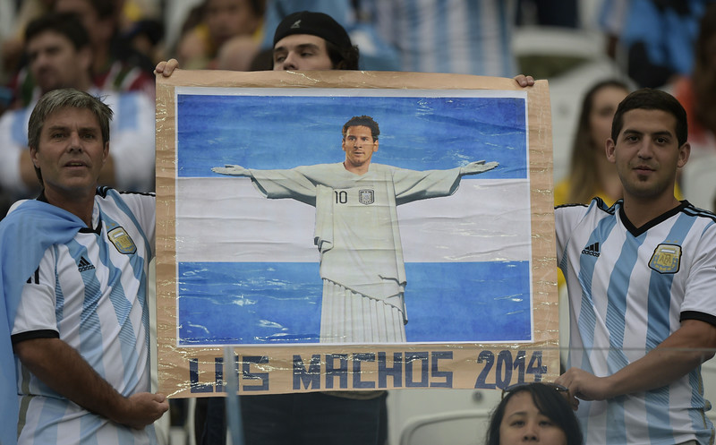 . Argentina\'s fans hold a poster of Argentina\'s forward and captain Lionel Messi as they await the kick off of the semi-final football match between Netherlands and Argentina of the FIFA World Cup at The Corinthians Arena in Sao Paulo on July 9, 2014.  (JUAN MABROMATA/AFP/Getty Images)