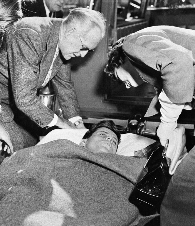 . Joseph P. Kennedy and Jaqueline Kennedy assist Sen. Kennedy on Nov. 9, 1960. The senator went to Florida to convalesce after a spinal operation.  Associated Press file