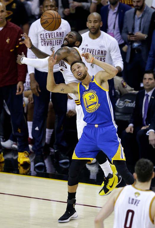 . Cleveland Cavaliers guard Kyrie Irving (2) and Golden State Warriors guard Stephen Curry (30) battle for a loose ball during the first half of Game 3 of basketball\'s NBA Finals in Cleveland, Wednesday, June 7, 2017. (AP Photo/Tony Dejak)