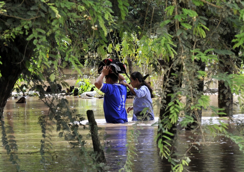 Description of . A couple wades through a flooded street, following heavy rains hitting the country, in Reyes, department of Beni, northeast Bolivia, on February 2, 2014. (AIZAR RALDES/AFP/Getty Images)