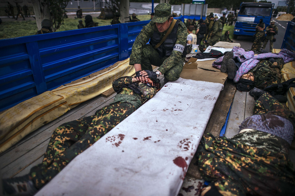 . A pro-Russian gunman touches the body of his friend in a truck at a checkpoint outside of the eastern Ukrainian city of Donetsk on May 23, 2014.  AFP PHOTO / DIMITAR DILKOFF /AFP/Getty Images