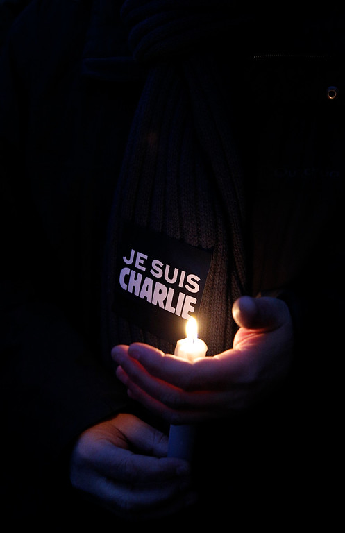 ". A man holds a candle and a sticker reading "" I am Charlie\"", during a demonstration in Paris, Wednesday, Jan. 7, 2015. Three masked gunmen shouting \""Allahu akbar!\"" stormed the Paris offices of a satirical newspaper, Charlie Hebdo, Wednesday, killing 12 people, including its editor, before escaping in a car. It was France\'s deadliest postwar terrorist attack. (AP Photo/Christophe Ena)"