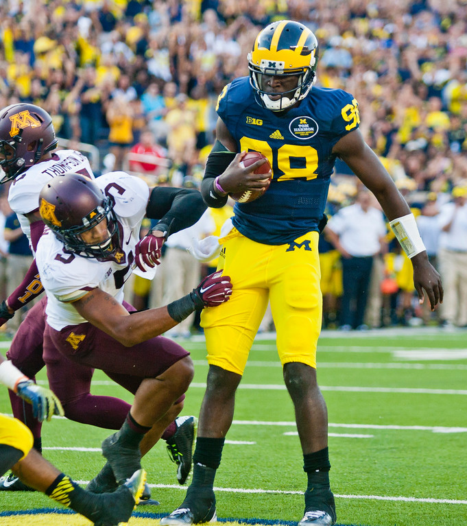 . Michigan quarterback Devin Gardner (98) scores a touchdown while knocking over Minnesota linebacker Damien Wilson (5) in the fourth quarter of an NCAA college football game in Ann Arbor, Mich., Saturday, Sept. 27, 2014. Minnesota won 30-14. (AP Photo/Tony Ding)