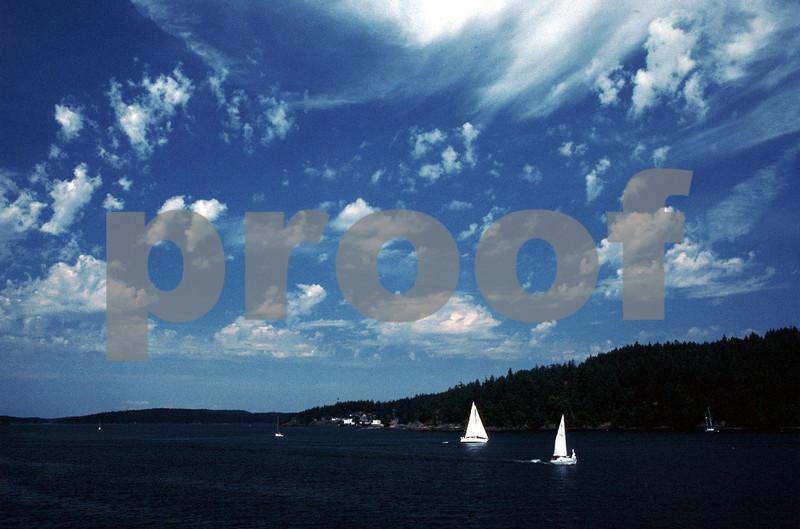 Sailboats ply the waters between the San Juan Islands.