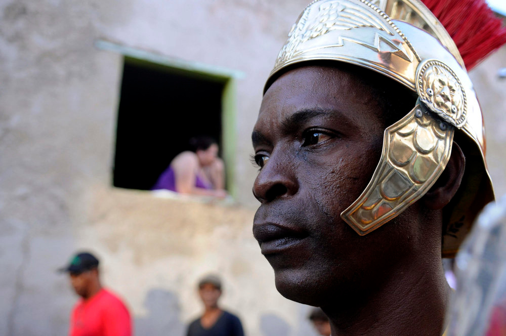 ". A resident watches actors and penitents taking part in a ""Via Crucis\"" (Way of the Cross) procession, which commemorates Jesus Christ\'s crucifixion during Holy Week in Santo Domingo March 29, 2013. Holy Week is celebrated in many Christian traditions during the week before Easter.    REUTERS/ Ricardo Rojas"