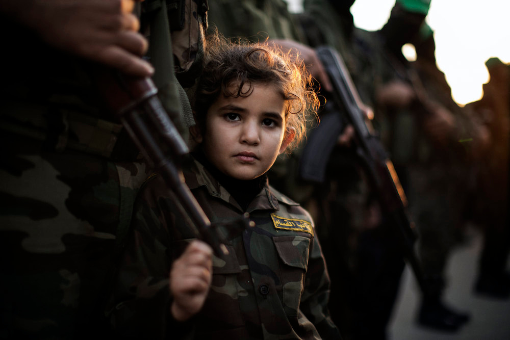 . A Palestinian girl dressed as a Ezzedine al-Qassam brigade member is seen holding the barrel of a gun during a march by Hamas armed wing in Beit Hanun on December 6, 2012. The Hamas government confirmed that the Islamist movement\'s exiled politburo chief Khaled Meshaal was due in the Gaza Strip to celebrate its 25th anniversary. MARCO LONGARI/AFP/Getty Images