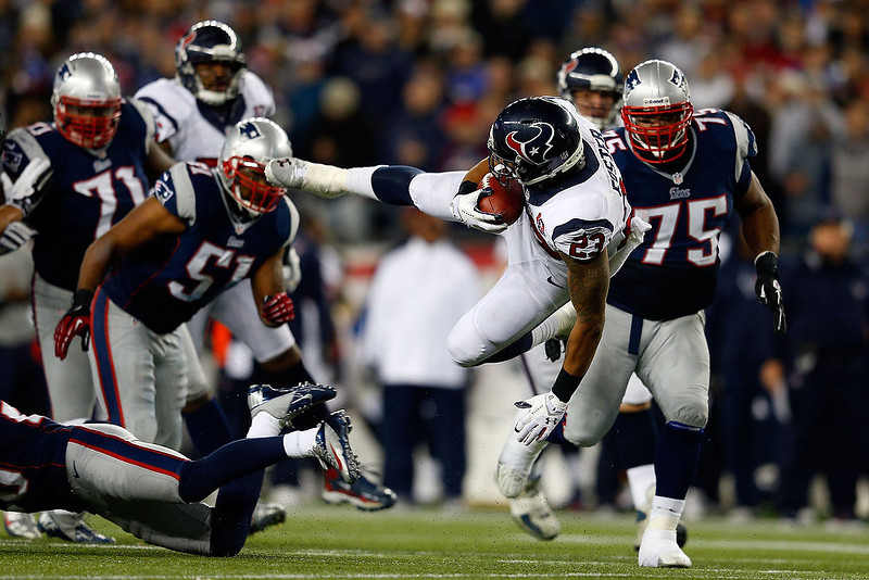 . Arian Foster #23 of the Houston Texans gets knocked off of his feet against the New England Patriots during the 2013 AFC Divisional Playoffs game at Gillette Stadium on January 13, 2013 in Foxboro, Massachusetts.  (Photo by Jim Rogash/Getty Images)