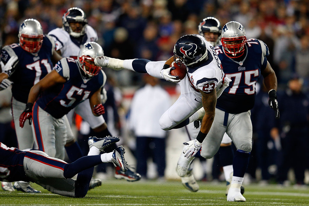 Description of . Arian Foster #23 of the Houston Texans gets knocked off of his feet against the New England Patriots during the 2013 AFC Divisional Playoffs game at Gillette Stadium on January 13, 2013 in Foxboro, Massachusetts.  (Photo by Jim Rogash/Getty Images)