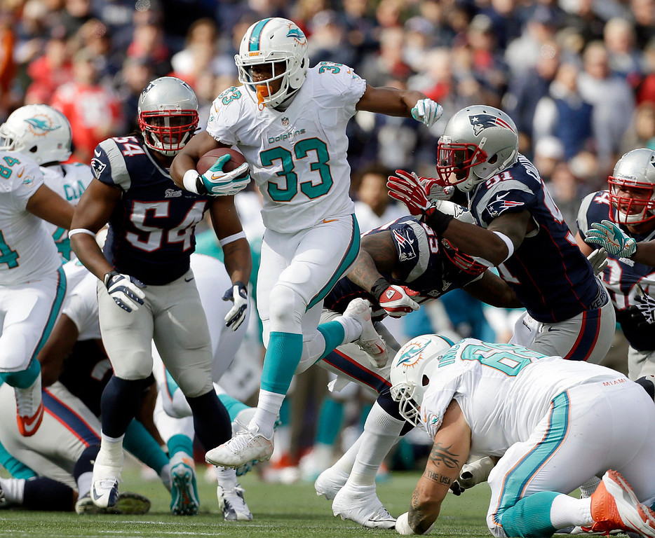 . Miami Dolphins running back Daniel Thomas (33) runs from New England Patriots linebackers Dont\'a Hightower (54) and Jamie Collins (91) in the second quarter of an NFL football game Sunday, Oct. 27, 2013, in Foxborough, Mass. (AP Photo/Steven Senne)