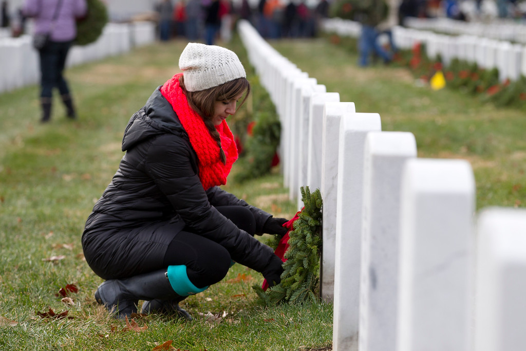 . Volunteer Nicole Battle helps lay holiday wreaths at graves at Arlington National Cemetery in Arlington, Va., Saturday Dec. 14, 2013, during Wreaths Across America Day. Wreaths Across America was started in 1992 at Arlington National Cemetery by Maine businessman Morrill Worcester and has expanded to hundreds of veterans\' cemeteries and other locations in all 50 states and beyond. (AP Photo/Jose Luis Magana)