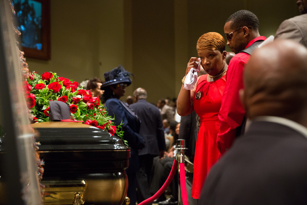 Description of . Lesley McSpadden stands at the casket the of her son Michael Brown during his funeral at Friendly Temple Missionary Baptist Church in St. Louis, Monday, Aug. 25, 2014. Hundreds of people gathered to say goodbye to Brown, who was shot and killed by a Ferguson, Mo., police officer on Aug. 9. The more than two weeks since Michael Brown's death have been marked by nightly protests, some violent and chaotic, although tensions have eased in recent days. (AP Photo/New York Times, Richard Perry, Pool)