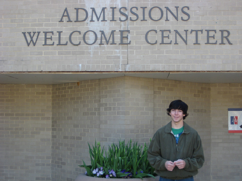 Alex standing at the Admissions Welcome Center. Walk up the stairs to ask questions.