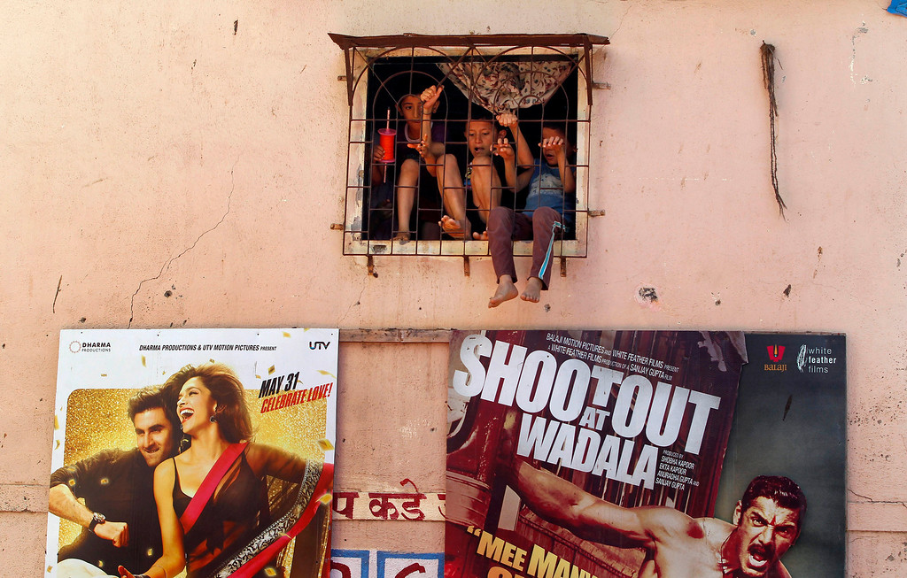 """. Children play behind a window of their house as Bollywood film posters are displayed on its wall in Mumbai, India, Friday, May 3, 2013. Four top Indian filmmakers have come together to make \""""Bombay Talkies,\"""" a short-film collection that hits theaters Friday to celebrate 100 years of Indian cinema. India\'s first full-length feature film \""""Raja Harishchandra,\"""" or \""""King Harishchandra,\"""" was released in 1913. Since then Indian cinema has become the largest producer of films in the world. India produced nearly 1,500 films last year, according to accounting firm KPMG. (AP Photo/Rajanish Kakade)"""