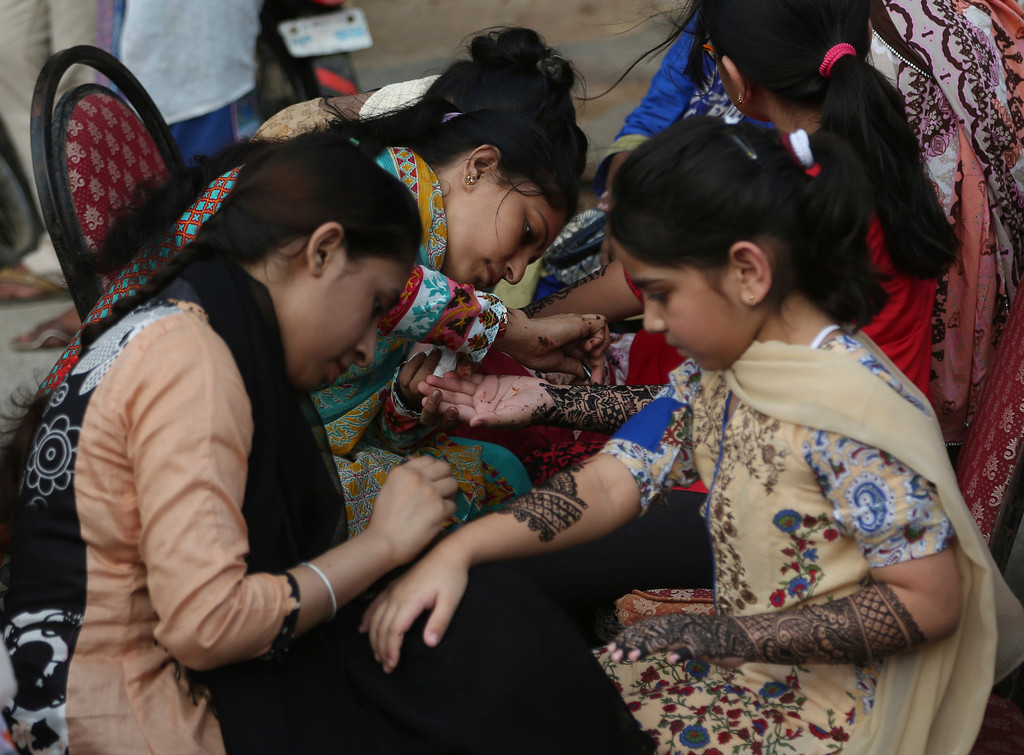 . Pakistani beauticians decorate the hands of customers with traditional henna in preparation for the Eid al-Fitr holiday to mark the end of the Islamic fasting month of Ramadan, in Karachi, Pakistan, Friday, June 15, 2018. Pakistanis will celebrate Eid al-Fitr on Saturday. (AP Photo/Shakil Adil)